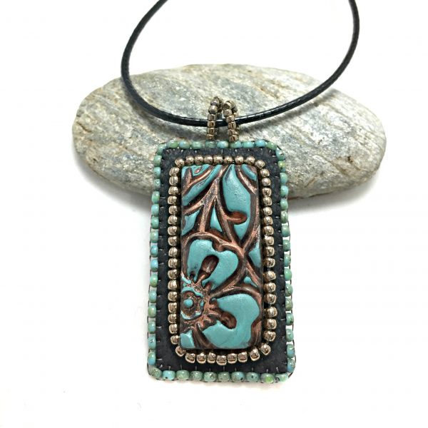 close up of patina leather pendant